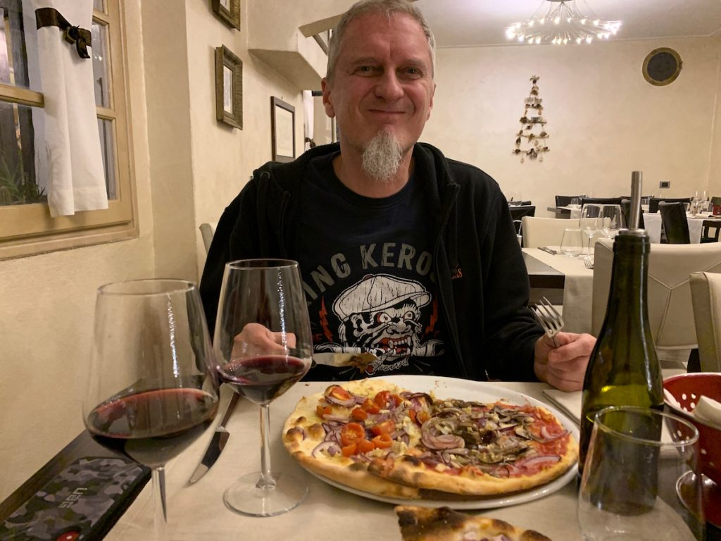 Vegan Tourists in Italy: Alex in the Pizzeria with a vegan Pizza Marinara, topped with veggies